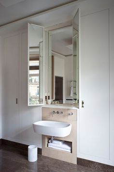 A New Take On Vanity - These angled medicine cabinet doors mirror outdoor views when open, and when closed, blend seamlessly into their built-in surrounds. Design by Pierre Yovanovitch.