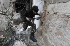 A fighter from the Al-Mujahideen army, which operates under the Free Syrian Army, walks through a hole in the wall on the Zeno street frontline in Aleppo November 18, 2014. REUTERS-Hosam Katan