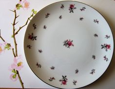 This beautiful Dinner Plate by Meito was made in Japan and is named Rosechintz. The pattern consists of delicate handpainted tiny pink roses on a white china background. Silver bands encircle the plate rim.