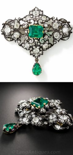 Victorian Emerald and Diamond Brooch. A brooch hand crafted in darkened silver over 18 karat yellow gold, displaying two emeralds: a 5.18 carat emerald-cut in the center and a 1.65 carat pear shape drop dangling below. Both gemstones exhibit a bluish-green hue, and are embellished by 7.50 carats of glittering, bright-white, old mine-cut diamonds set in a scrolling foliate motif. 2 and 1/4 inches (11.20 x 9.80 mm).