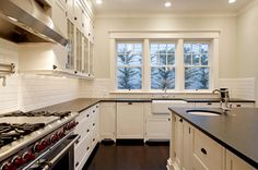 Love the six over one windows above the sink, white cabinets, and subway tile.
