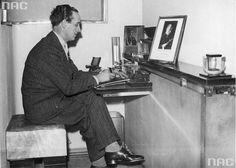 """Mistrz fryzjerski Antoni """"Antoine"""" Cierplikowski siedzi przy biurku podczas pracy. Na półce stoją fotografie Benito Mussoliniego i Bolesława Wieniawa- Długoszowskiego."""