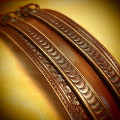 This Unique Matara Design leather cuff uses natural american vegetable-tanned leather and is Hand tooled,scribed,edged and stamped with an original border design. It is 2-3/4 wide and runs 2 studded straps over the main cuff . I use Western leather techniques and no electric tools. It is finished in a beautiful sienna brown saddle dye, distressed and hand rubbed with custom paste and lotion creating a unique vintage look. Aged nickel roller buckles and vintage copper rivets provide the c...