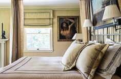 """In the master bedroom, Timothy used a similar fabric to upholster the walls and make the shades and the bed drapes. """"Upholstering a bedroom cuts sound and creates a very cozy, intimate feeling."""""""