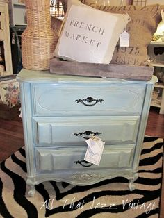 I like the combination here; duck egg blue nightstand with the browns and greys of the wood and burlap.