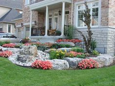 This slight slope was tastefully designed, with a nice balance of large rocks and plants. A nice decorative rock bed in the front adds some more interest. Picture compliments of www.ogslandscape.ca