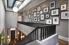 Gray painted walls are a wonderful backdrop for a collection of black and white photos set up in a gallery wall. The white matting and white floor base create a dramatic contrast.