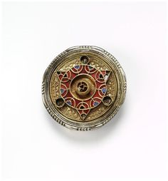 The ornate and colourful decoration on this brooch consists of cloisons (cells) inlaid with garnets and blue glass paste. The front is further enriched with filigree wires. The garnets themselves were possibly obtained by sea trade from India.  A brooch like this is an elaborate form of safety pin, with the pin hidden on the back of a decorative disk. Women who could afford it would wear such a brooch to close a cloak or veil over their chest.