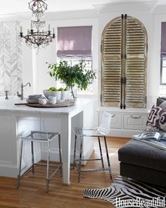 Shutters for doors? A crystal chandelier and weathered wood shutters add the patina of age, which softens all the cool white marble and stainless steel. Designed by Doug Davis and Hannon Kirk Doody