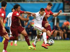 United States' Clint Dempsey, centre, is challenged by Portugal's Bruno Alves, left, and Portugal's Miguel Veloso, right,
