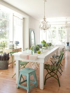 the green chairs and aqua stool offset by the white room and table, and most importantly all the large open windows flooded with light and the dapple of green outside... <3