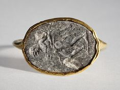 Satyr with drinking bowl and a shepherd's crook. Graeco-Roman ringstone in gold ring, 30 BC-200  Chalcedony, gold. 1,6 x 1,2 cm Inventory number: I388