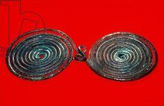 Double fibula, from Hallstatt, c.750-400 BC (bronze) Creator     Iron Age Description     Brillenfibel; Location     Praehistorisches Museum, Hallstatt, Austria Medium     bronze