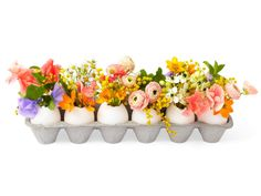 Easter decorating ideas | HGTV | Hatch a Teeny-Tiny Vase | Pierce the top of a raw egg with a pin, then gently poke the hole with your finger to widen it. Empty the whites and yolk, and rinse the shell with water. Fill with delicate flowers like sweet pea and mimosa. Put a single shell in an eggcup or arrange a dozen in a carton. Eggcup: Try Etsy for a variety of styles.