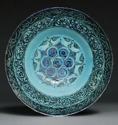 A KASHAN TURQUOISE AND BLACK PIERCED POTTERY BOWL CENTRAL IRAN, LATE 12TH OR EARLY 13TH CENTURY