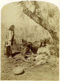 Photograph (black and white); portrait of two Ute women seated on the ground underneath a tree, both wearing hide dresses, they are holding hands; one of the women is wearing bead neck ornaments, and is created a piece of quillwork; a basket is on the ground next to the women; an Ute man is standing behind the women, wearing a hide fringed tunic, leggins, moccasins, and beads in his hair; trees are in the background; Utah, United States of America.  Albumen print