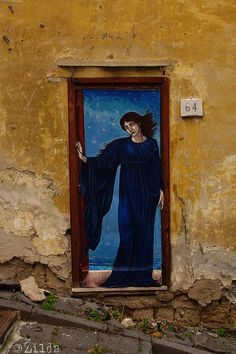 Door with painting of woman against night sky. Naples, Italy
