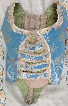 Corsage de robe à l'anglaise en Ras de Sicile, vers 1785. Soie, effet damas bicolore orné de fleurs exotiques bleu Nattier liseré blanc effet argent datant de 1760 environ. Doublure en taffetas léger vert tendre et rayures ombrées pastel se laçant devant par de petits oeillets cousus main. Dos ajusté en pointe. Les compères se croisent par un jeu de pattes et boutonnières alternées, bordées d'une frange d'effilé en soie crème soulignant décolleté et pourtours et les pattes d'accrochage à…