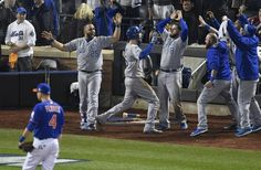 Kansas City Royals first baseman Eric Hosmer, in batting helmet, is swarmed by teammates after he scored the tying run in the ninth inning during game five of the World Series on Sunday, November 1, 2015 at Citi Field in New York.