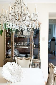 The china cabinet is made of mirrored glass with intricate veining, giving it a subtle pattern. Source: Kassie Borreson
