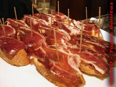 """Pinchos Iberico Ham on Long Bread """"Pintxos Jamon Iberico""""  This Basque pintxos recipe consists of a slice of crispy long bread loaded with a fair layer of Iberico ham which is also called Pata Negra (Black Foot). This seems too simple, and actually it is a very easy recipe, but it is also absolutely delicious!  This style of tapas on bread is very common in the tapas restaurants and bars of Bilbao,"""