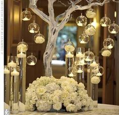 White votive candles hanging from a white branch with white flowers - very pretty table centerpiece!