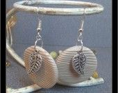 Boucles d'oreilles pendantes avec rond imitation bois en Fimo et une breloque feuille Boucles de 3cm de diamètre imitation bois avec une petite breloque en métal en forme de feuille sur le devant
