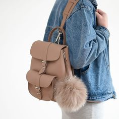 Colour: Deep Taupe100% LeatherSmall Size BackpackMatching colour pom pomTwo adjustable shoulder strapsOne Front PocketMade in England