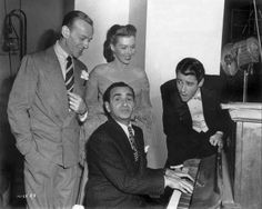 Composer Irving Berlin seated at piano, surrounded by Fred Astaire, Ann Miller and Peter Lawford on the set of Easter Parade (1948)