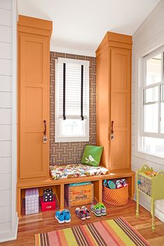 Thanks to a sun-kissed color scheme, plenty of natural light, and a bench that's also a window seat, this mudroom by builder Bret Franks is a place to hang out as well as hang up. Slender cabinets extend all the way to the pitched ceiling, maximizing vertical storage.