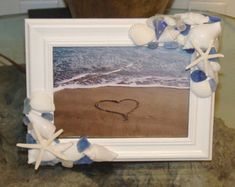 We are glad to offer this custom, made to order listing for a lovely beach frame made with hand tumbled sea glass, white natural sea shells, starfish, and sand dollars. All on a artist painted white frame. We can also offer y. Seashell Art, Seashell Crafts, Beach Crafts, Seashell Frame, Beach Picture Frames, Beach Frame, Seaside Decor, Coastal Decor, Coastal Living