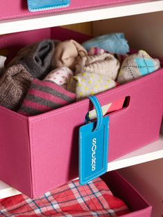 Organize closet with colorful canvas bins and leather luggage tags as labels