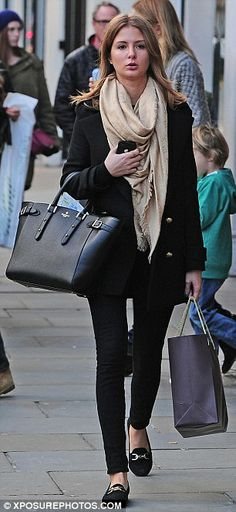 The style queen: Millie accessorised her black coat well with a Louis Vuitton cream scarf and suede shoes