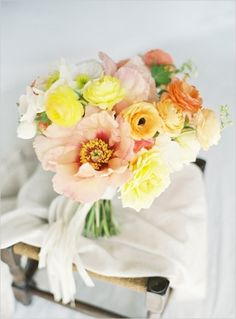 Bridal bouquet of cafe au lait dahlias, dusty miller, pink ranunculus, light pink lisianthus, silver brunia berries, and pale pink and
