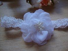 Faixa trançada em perolas,florzinhas brancas com aplicação de perola. elastico macio e confortavel na nuca. Disponivel tambem na cor perola. Informe a idade da sua linda.