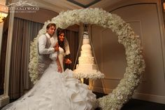 Bride and groom take position for the Halo Hanging Wedding Cake cutting ceremony. Suspended from our custom floral floral arch @ The Berkeley Hotel Knightsbridge London suspended cakes / chandelier cake / Hanging Cakes / Unique wedding cakes