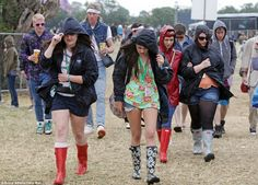 Trying to keep dry: Festival-goers wrapped up against the elements when there was a little rain at the Glastonbury Music Festival at Worthy Farm