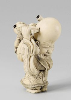 An amusing and fine ivory netsuke of Fukurokuju and karako, by Masakazu. 19th century. Fukurokuju stands with a scroll tied to his gnarled staff and a tray to catch the falling hair that a karako sitting on a bag at Fukurokuju's back is shaving. Hair tufts and scroll knobs of black horn. Signed Masakazu in an oval reserve.