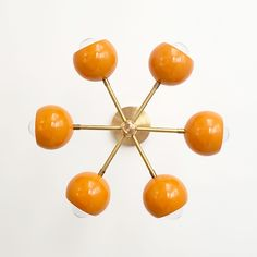 Flush mount ceiling light fixture with orange globe shades and brass accents. Perfect for Mid Century modern inspired bedrooms, nurseries, bathrooms, and much more. Orange Interior, Modern Interior, Monochrome Interior, Interior Design, Ceiling Light Fixtures, Ceiling Lights, Ceiling Lamp, Baby Room Design, Nursery Design