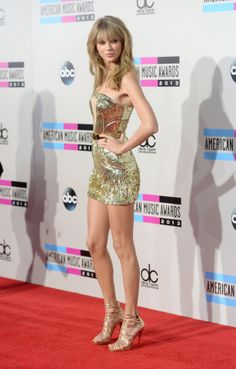 Taylor swift had gold everything at the AMAs, a gold background, dress, shoes, and others it was so gold
