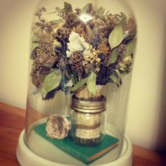 After our wedding I dried my bridal bouquet by hanging it upside down for a month. I sprayed the dried flowers with a UV protectant spray and placed them on display in our home in an oversized glass cloche. My bouquet was very special to me and I love how this turned out. #cloche #bouquet #wedding