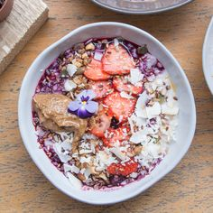 A delicious Porridge bowl topped with strawberries, coconut flakes, almond butter and more ... by 26 Grains / London