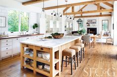 A spacious farmhouse kitchen with pendant lights, marble-topped kitchen island and Seagrass stools. @cottagesgardens