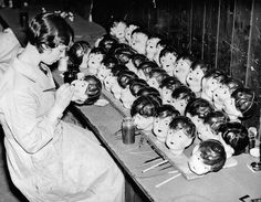 A doll worker in a factory in England painting doll heads, 1935
