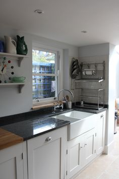 Black and greys flecked granite worktop with double ceramic farm sink. Granite works for practicality around water better than the oak worktop and balances the Rangemaster black on the opposite side.