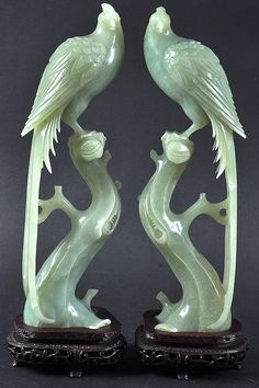 A PAIR OF EARLY 20TH CENTURY CHINESE CARVED GREEN JADE BIRDS modelled upon naturalistic outcrops. One repaired. Jade 10.5ins high.