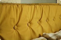 Headboard from foam wrapped in fabric and tufted with covered buttons.  Guest room??