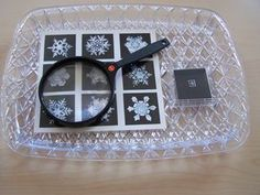 Matching snowflakes, small and larger using a magnifying glass.