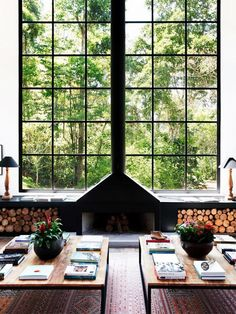 A perfectly placed chimney lends height and dimension. Fresh cut logs and floor-to-ceiling windows add to the organic symmetry of this sublime, modern space.
