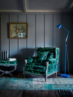 The Margot chair in marble butterfly positioned beside a blue floor lamp. Introducing Matthew Williamson's first ever bespoke furniture collection. Created in collaboration with Nottingham-based sofa manufacturer Duresta, the designs comprise five upholstery ranges and unique occasional pieces.
